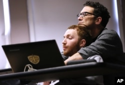 Sam Alexander holds his son, Ben, during a class for screenwriting at Tulane University in New Orleans. In his classes, Ben, who has nonverbal autism, sits with his dad at his side. Photo taken March 2, 2016. (AP photo)