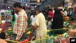 People are seen buying essential food staples at a supermarket in Doha, Qatar, Monday, June 5, 2017. Fears about food shortages came after some Gulf nations ended diplomatic relations with Qatar.