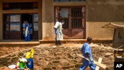 کارمند سردخانه ای در شهر بنی کنگو در حال ضدعفونی کردن ورودی سردخانه، و مرد دیگری که صلیب چوبی برای قبر یکی از کشته شدگان در دست حمل می کند.