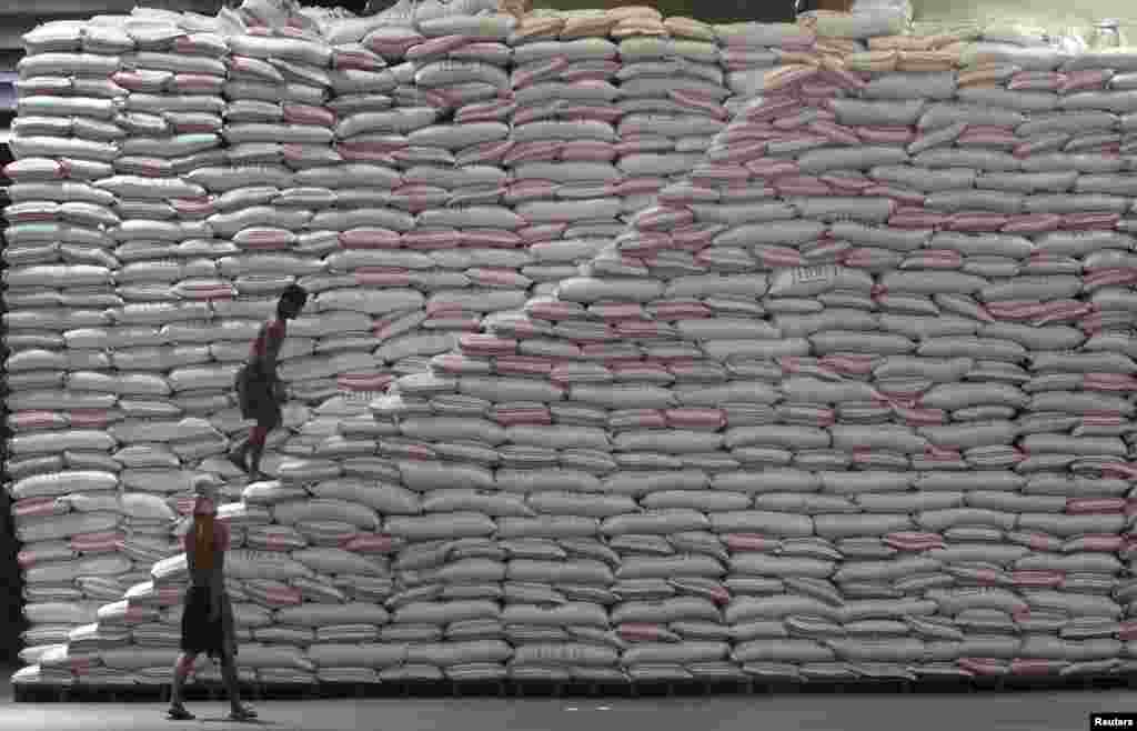 A worker walks up a pile of sacks of rice at a warehouse of the Philippines National Food Authority in Manila.