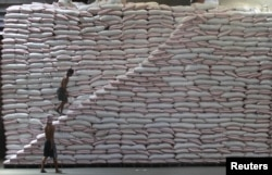 FILE - A worker walks up a pile of rice at a warehouse of the Philippines National Food Authority in Manila, May 12, 2015.