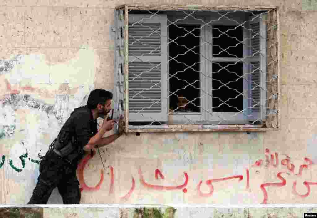 지난달 30일 시리아 알레포시에서 집 안에 있는 아동에게 피신하라고 당부하는 반군 병사.