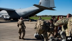This Oct. 29, 2018 photo provided by the U.S. Air Force shows deployers from Headquarters Company, 89th Military Police Brigade, Task Force Griffin getting ready to board a C-130J Super Hercules from Little Rock, Arkansas, at Fort Knox, Kentucky.