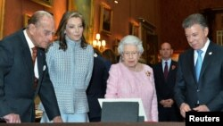 From left, Prince Phillip, Maria Clemencia Rodriguez de Santos, Queen Elizabeth and President Juan Manuel Santos look at Colombian items from the Royal collection in the picture Gallery of Buckingham Palace, November 1, 2016.