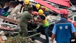 Rescatistas sacan un cuerpo de entre los escombros de un edificio derrumbado en la provincia de Preah Sihanouk, en Camboya, el 22 de junio de 2019. (Nokorwat News via AP)