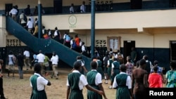 FILE - Liberian children line up to enter classrooms.