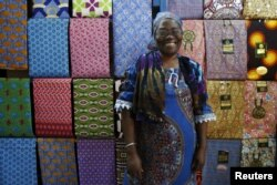 FILE - Fofanan Man, a 59-year-old businesswoman, poses for a photograph in front of textiles in her shop in Bouake, Ivory Coast, Feb. 10, 2016.