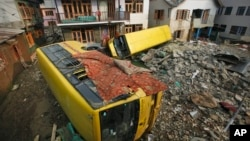 Bis sekolah yang terseret arus saat banjir bandang empat minggu yang lalu, terlihat masih teronggok di area permukiman penduduk di wilayah Srinagar, India (1/10).