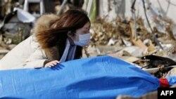 Bà Tayo Kitamura, 40 tuổi, quỳ bên thi hài mẹ là bà Kuniko Kitamura, 69 tuổi. Các nhân viên cứu hộ tìm thấy xác bà Kitamura trong ngôi nhà đổ nát ở Onagawa, ngày 19 tháng 3, 2011.