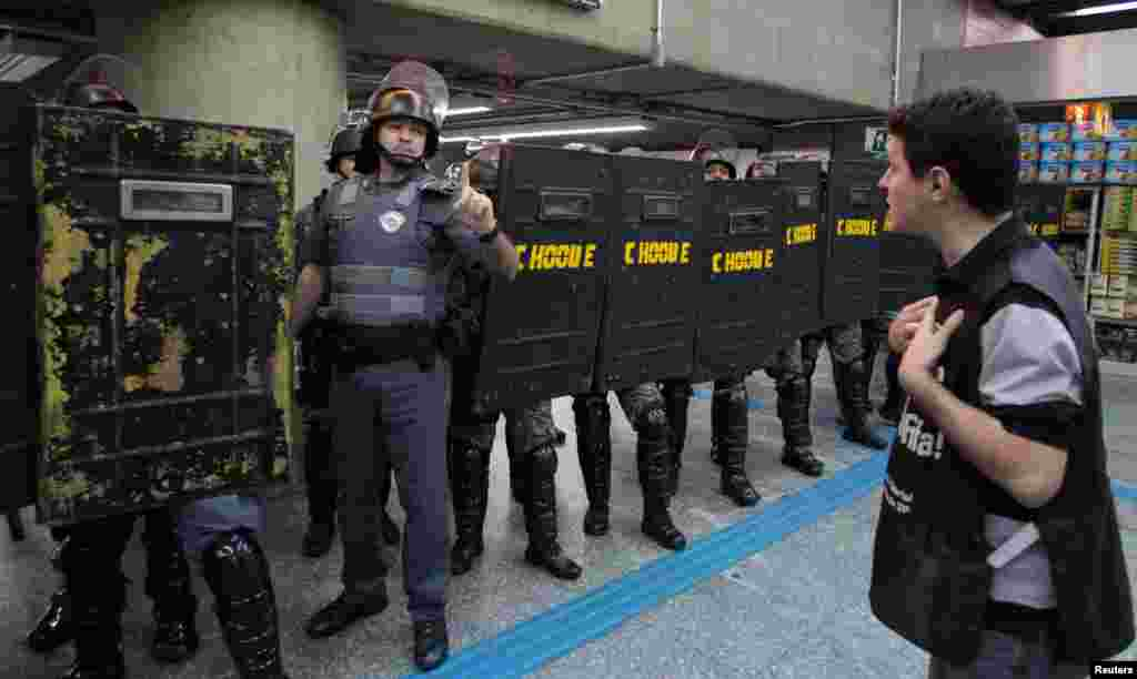 A man stands in front of riot police inside Ana Rosa subway station during the fifth day of metro workers' protest in Sao Paulo, Brazil, June 9, 2014.