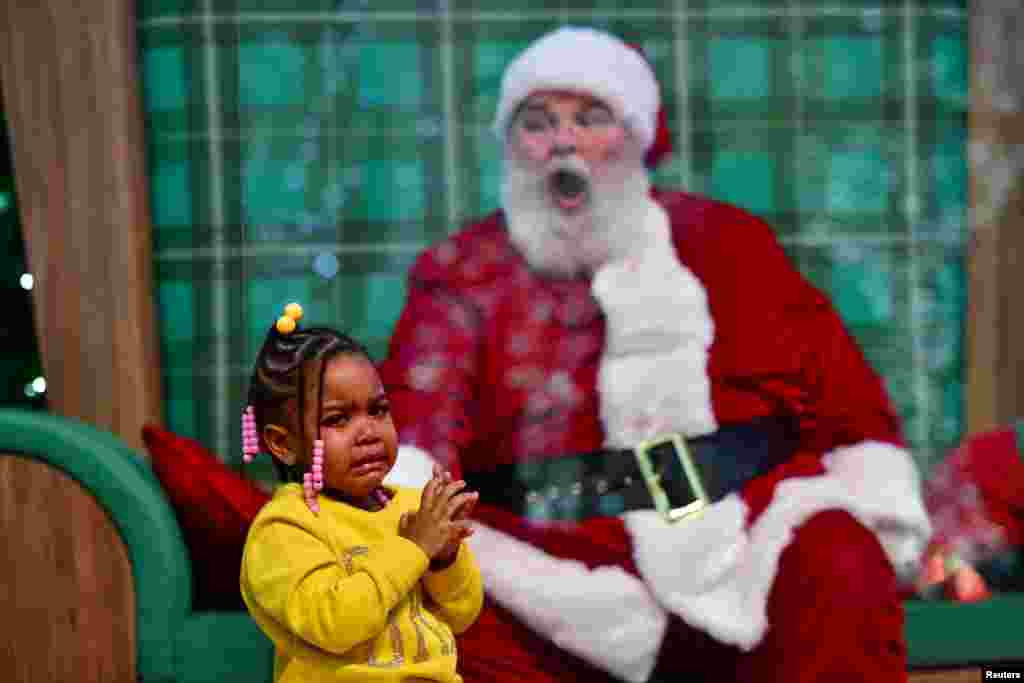 Majesty Davis, 3, cries during a visit to Santa Claus, who sits behind a plexiglass divider due to the COVID-19 pandemic, at the Willow Grove Park Mall in Willow Grove, Pennsylvania, Nov. 14, 2020.