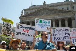 Demonstrators protest against a Supreme Court decision on immigration outside the New York Supreme court, Friday, June 24, 2016, in New York.