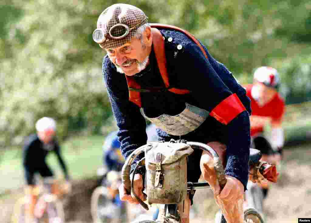 "Luciano Berruti rides a vintage bicycle on a gravel road during the Strade Bianche section of the ""Eroica"" cycling race for old bikes, in Gaiole in Chianti, Italy, Oct. 2, 2016."