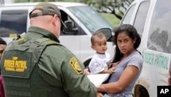 Una madre inmigrante de Honduras sostiene a su hijo de 1 año mientras se entrega a las autoridades fronterizas estadounidenses el lunes, 25 de junio de 2018 cerca de McAllen, Texas.