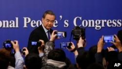 2018年3月8日中国人大会议期间,中国外交部长王毅在北京新闻中心举行记者招待会后, 记者纷纷拍摄。