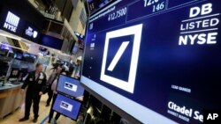 Traders walk by the post where Deutsche Bank is traded on the floor of the New York Stock Exchange, Monday, Sept. 26, 2016.