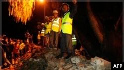Nhân viên cứu hộ và người dân Nepal đứng nhìn bức tường của Tòa đại sứ Anh bị sụp đổ, giết chết 3 người đi đường sau 1 trận động đất tại Katmandu, Nepal, Chủ Nhật 18/9/2011