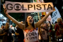 "A demonstrator holds a sign that reads in Portuguese ""Coup leader "" during a march against acting President Michel Temer and in support of Brazil's suspended President Dilma Rousseff in Rio de Janeiro, Brazil, Aug. 29, 2016."