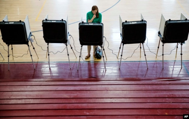 A voter casts a ballot in Georgia's primary election at a polling site in a high school gymnasium in Atlanta, March 1, 2016.
