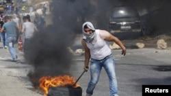 Seorang demonstran Palestina menyeret ban yang terbakar dalam bentrokan dengan pasukan Israel di kota Tepi Barat Hebron, 18 Oktober 2015.