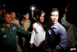 FILE - Yeang Sothearin (R) and Uon Chhin, former journalists for U.S. founded Radio Free Asia (RFA), who have been charged with espionage, leave Prey Sar prison after being freed on bail, in Phnom Penh, Cambodia, Aug. 21, 2018.