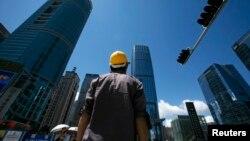2009年7月16日,一名建築工人在深圳商業區過馬路。 (路透社照片)