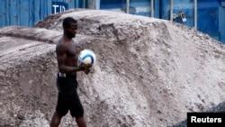 Un garçon circule avec un ballon dans une rue à Bata, Guinée équatoriale, 7 février 2015.