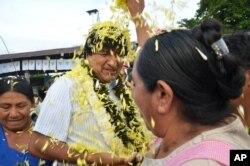 ຊາວສວນປູກຕົ້ນ ໂຄຄາ ຕ້ອນຮັບປະທານາທິບໍດີ ໂບລີເວຍ ທ່ານ Evo Morales (ກາງ) ໃນຂະນະທີ່ທ່ານໄດ້ເດີນທາງຮອດສູນເລືອກຕັ້ງເພື່ອ ລົງຄະແນນສຽງທີ່ພາກພື້ນ Villa 14 de Semtiembre. 21 ກຸມພາ 2016.