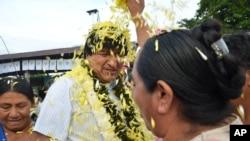 A coca farmer welcomes Bolivia's President Evo Morales, center, as he arrives to a polling station to vote in Villa 14 de Septiembre, in the Chapare region, Feb. 21, 2016.