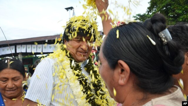 A coca farmer welcomes Bolivia's President Evo Morales, center, as he arrives to a polling station to vote in Villa 14 de Septiembre, in the Chapare region, Feb. 21, 2016.