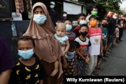 Sejumlah warga antre menerima bantuan dari Presiden Jokowi di tengah kebijakan PPKM di Jakarta (foto: dok).