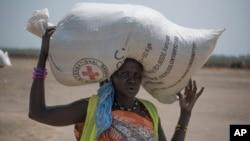 2017年4月11日拍攝的這張照片中,一名蘇丹婦女收到紅十字會發放的食物後,回到家中。
