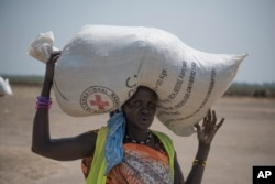 FILE - In this photo taken April 11, 2017, a woman walks back to her home after receiving food distributed by the Red Cross in South Sudan.