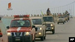 An image grab taken from Bahrain TV shows 'vanguard' of a contingent of Gulf troops arriving in the unrest-wracked Kingdom of Bahrain across a causeway from Saudi Arabia, March 14, 2011