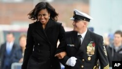 First lady Michelle Obama is escorted by USS Illinois Chief of the Boat, Master Chief David DiPietro during a commissioning ceremony for the U.S. Navy attack submarine USS Illinois, in Groton, Conn., Oct. 29, 2016. The submarine is named for Obama's home