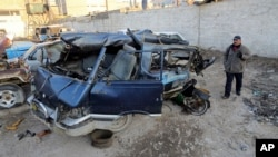 An Iraqi man inspects damaged vehicles in a car bomb attack in Baghdad, Iraq, Dec. 16, 2013.
