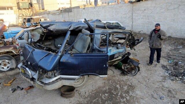 An Iraqi man inspects damaged vehicles in a car bomb attack in Baghdad, Iraq, Dec. 16, 2013.