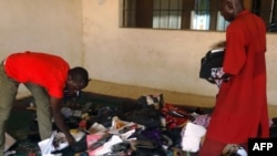 A student aided by a porter rummages through personal effects abandoned by students at the Federal College of Education in the northern Nigerian city of Kano, Sept. 17, 2014, following an attack by gunmen who stormed the lecture hall opening fire on students.