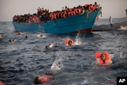 FILE - Migrants jump into the water from a crowded wooden boat as they are helped by members of an NGO during a rescue operation at the Mediterranean sea, about 13 miles north of Sabratha, Libya, Aug. 29, 2016.