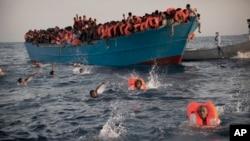 Des migrants, ressortissants d'Erythrée pour la plupart, sautent dans l'eau d'un bateau bondé lors d'une opération de sauvetage en pleine Méditerranée, à Sabratha, Libye, 29 août 2016.