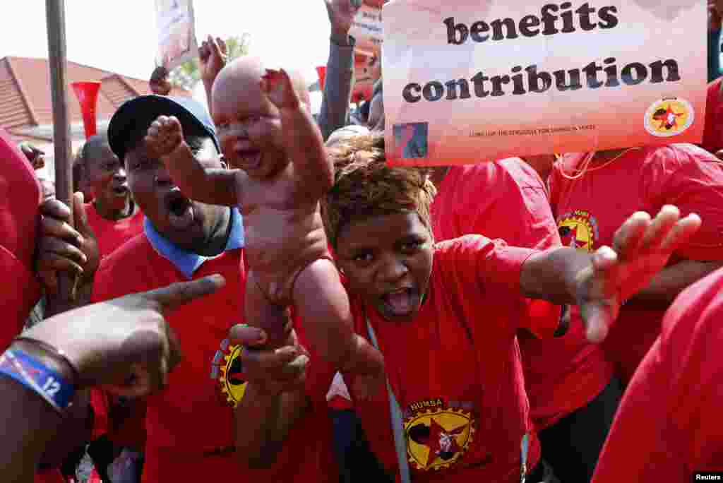 A member of the National Union of Metalworkers of South Africa (NUMSA) holds a baby doll as strikers march in Cape Town, Sept. 9, 2013.