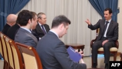 Assad Rossiya elchisi Azatulla Xolmuhammadov va boshqa rasmiylar bilan ko'rishayapti. 22-mart, 2015-yil.
