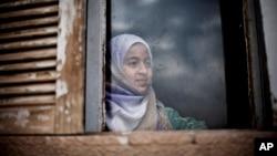 一叙利亚库尔德女孩在废弃大楼窗口向外眺望