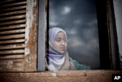 A Syrian girl from Aleppo looks outside a window of an abandoned building where her and several families took refuge due to fighting between Free Syrian Army fighters and government forces in the northeastern city of Qamishli, Syria, Thursday, Feb. 28, 2013. (AP Photo/Manu Brabo)