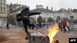 Một thanh niên nhảy qua thùng rác bị đốt cháy trong cuộc đụng độ ở Lyon, miền trung nước Pháp, ngày 19/10/2010