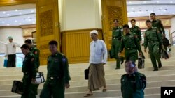 "In this Sept. 17, 2014 photo, a member of Myanmar's Lower House with a silk turban known as a ""gaun baun,"" leaves Myanmar's Upper House in Naypyidaw, Myanmar. The civilians elected to Myanmar's bicameral legislature are required to wear hats when taking the floor. Their appointed military colleagues are not. (AP Photo/Gemunu Amarasinghe)"
