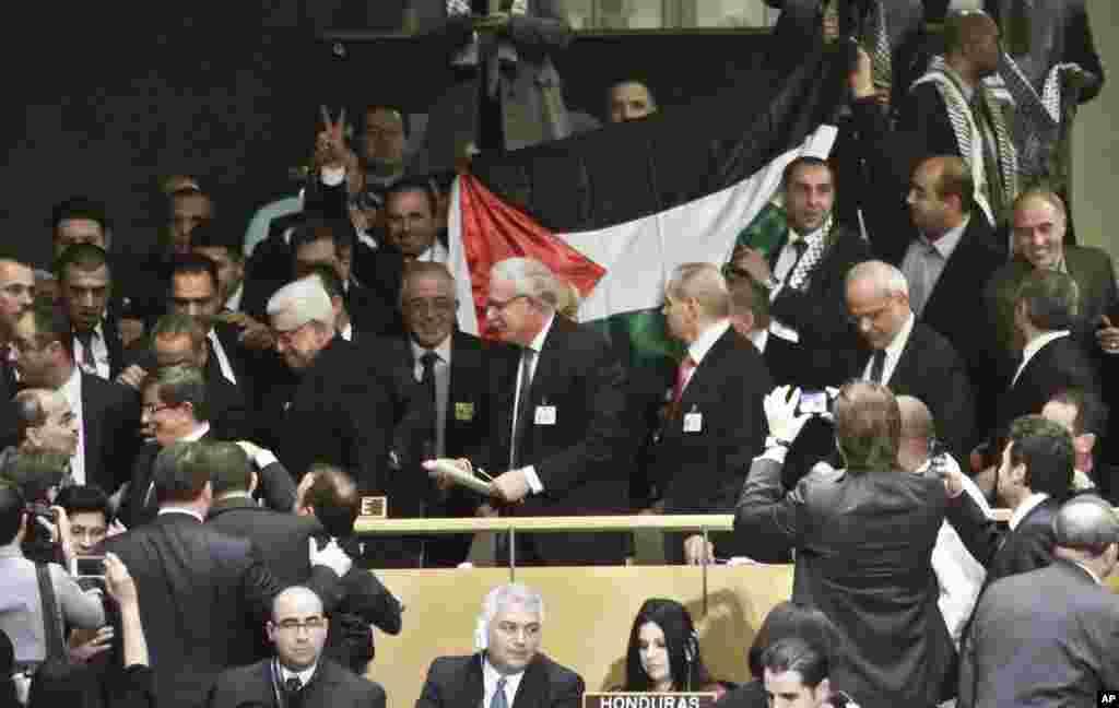 2012年11月29日,巴勒斯坦人领袖阿巴斯在联大表决后带领代表团离开联合国,他的身后是一面巴勒斯坦旗帜。