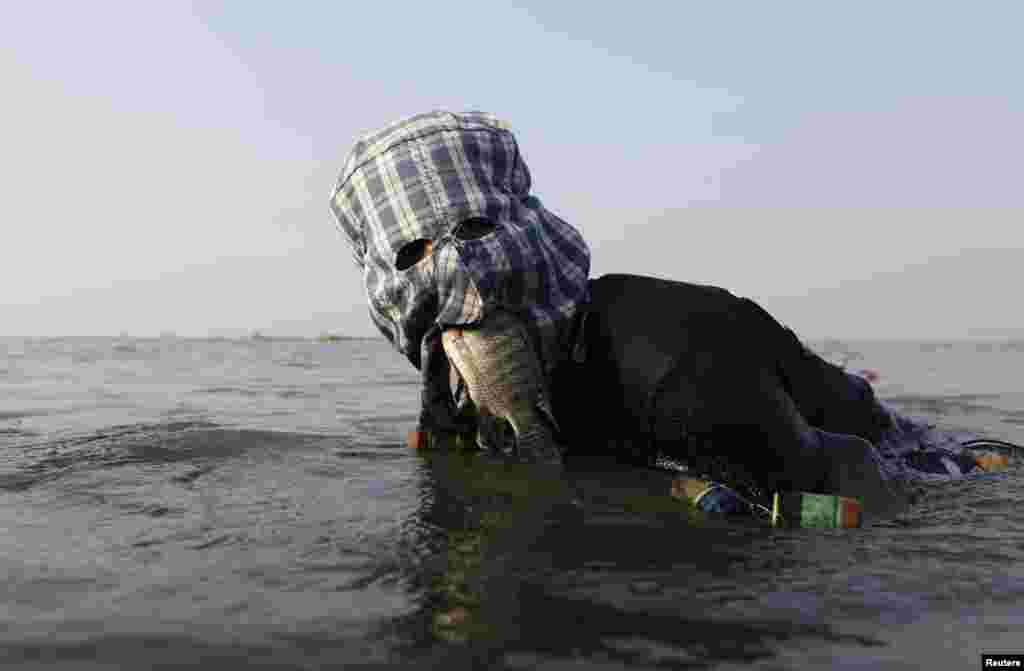 Fisherman Ompong Vargas, 39, who wears a facial mask made of fabric to protect his skin from getting darker, holds a fish in his mouth as he searches a net at Laguna de Bay in Taguig City, Metro Manila, Philippines, May 24, 2013.