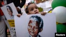 Bé trai 2 tuổi cầm hình cựu Tổng thống Nam Phi Nelson Mandela.