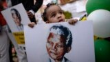 Two-year-old Precious Mali holds a picture of former South African President Mandela.